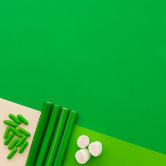 緑の背景にマシュマロ、カプセル、甘草キャンディーの高い角度のビュー