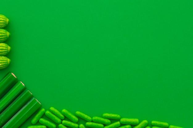 緑の背景に様々な甘いキャンディーのオーバーヘッドビュー