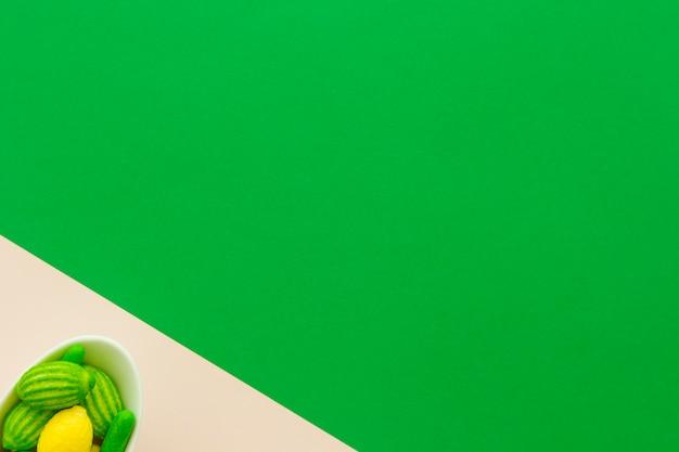 デュアルカラフルな背景にボウルのレモンキャンディーの高い角度のビュー