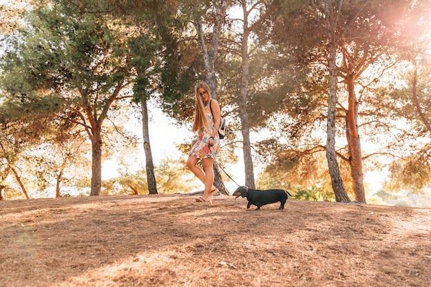 庭で彼女の犬と歩いている女性