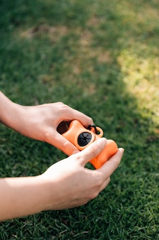 緑色の草の上で飼い放し子犬を保持している所有者のクローズアップ