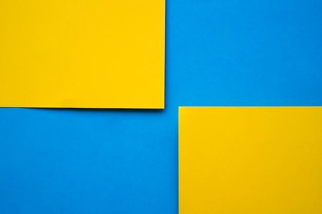 Две желтые картонные бумаги на синем фоне