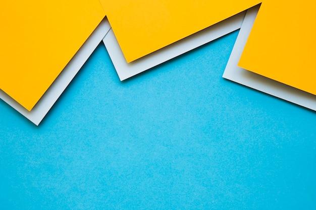 青色の表面に黄色の灰色の厚紙紙のオーバーヘッドビュー