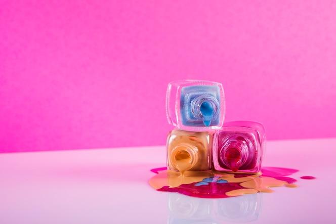 カラフルなマニキュアがピンクの背景にこぼれる