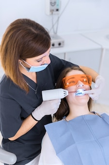 女性患者にホワイトニングレーザーを使用する歯科医