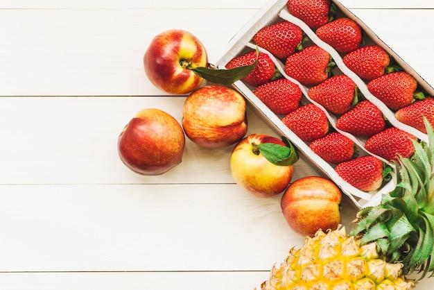 Верхний вид ананаса; яблоки и клубника на деревянной поверхности