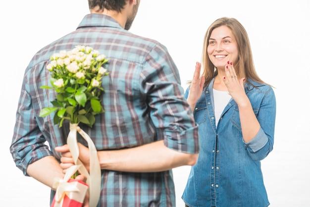Человек скрывает цветок и подарок за спиной перед улыбающейся девушкой