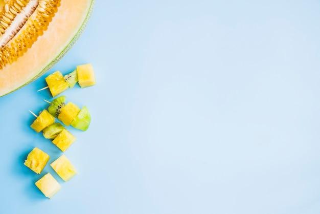 青色の背景に半分のメロンの近くにキウイとパイナップルのカノペ