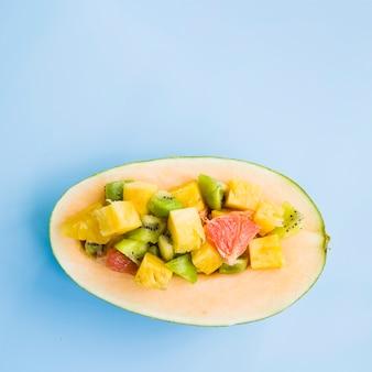 青い背景に果物のスライスと半減メロン