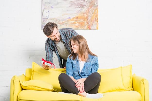 ソファに座っている彼の幸せなガールフレンドに贈り物を与える男