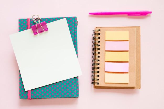 ピンクの背景に様々な文房具の高い角度のビュー