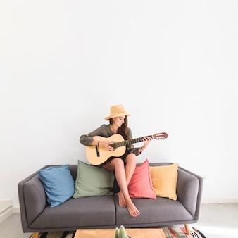 家でギターを弾いている帽子をかぶっている十代の少女