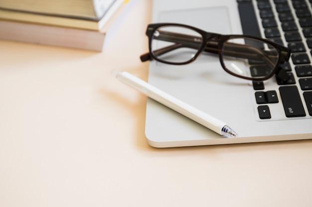 ノートパソコンのキーパッドでペンと眼鏡のクローズアップ