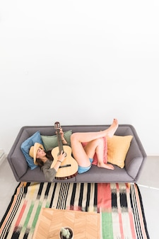 ギターを弾くソファに横たわっている幸せな十代の少