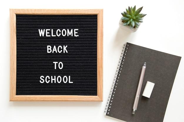 白い背景上の文房具の近くのスレートの学校のテキストに戻ってようこそ