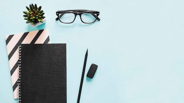 ノートブックの高い角度のビュー;鉛筆;青い背景に消しゴムと眼鏡