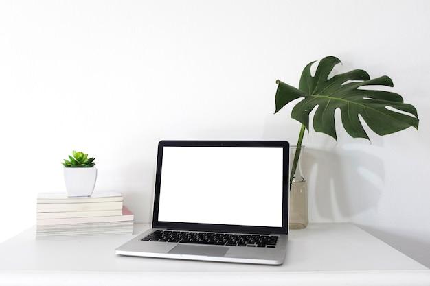 オフィスのデスク上に白い画面が空白のラップトップ