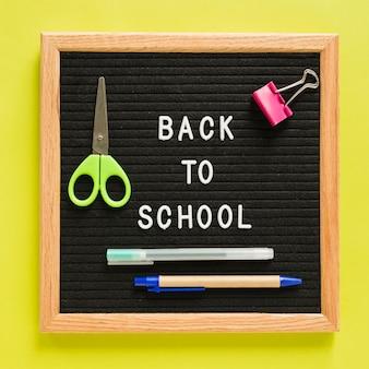 黄色の背景を持つ文房具とスレートの学校のテキストに戻る
