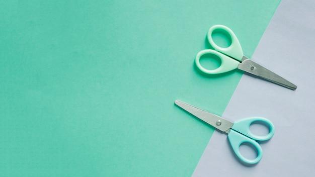 Вид сверху двух ножниц на двухцветном фоне