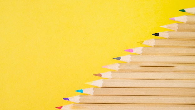 黄色の背景に様々なカラフルな鉛筆の高さのビュー