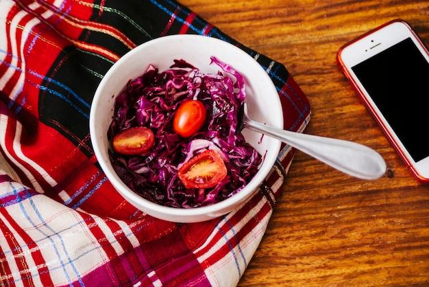 Повышенный вид свежих помидоров и красной капусты в миске возле смартфона