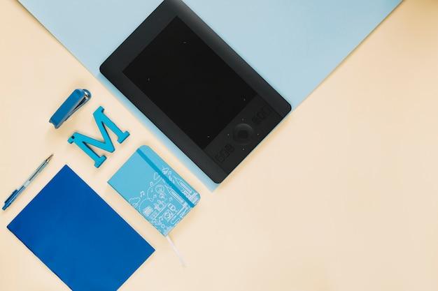 カラフルな紙の背景にグラフィックデジタルタブレットと文房具