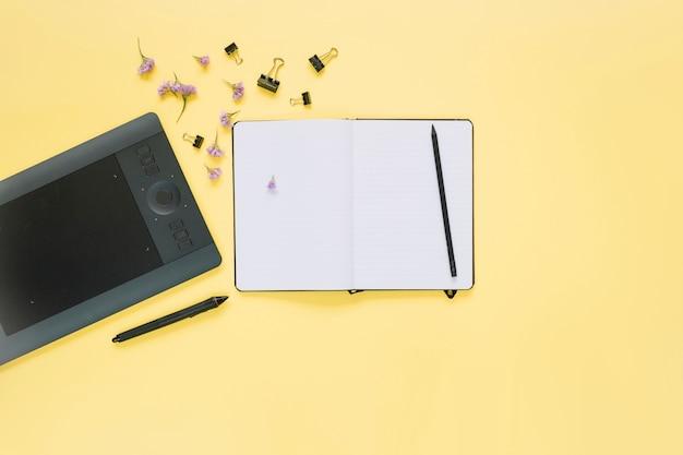 黄色の表面上に開いたノートブックとグラフィックデジタルタブレットの高められたビュー
