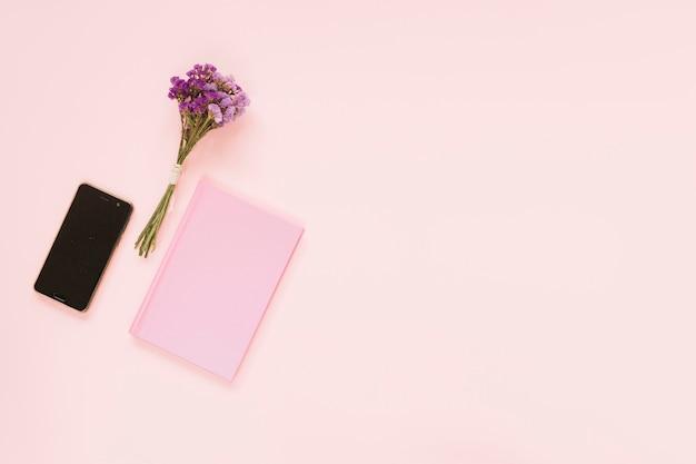 ラベンダーの花の束;ピンクの背景に携帯電話と日記