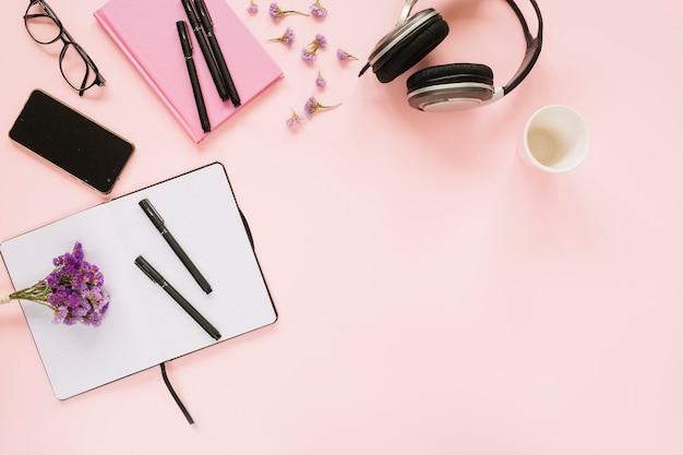 ピンクの背景にオフィスの文房具と携帯電話とラベンダーの花