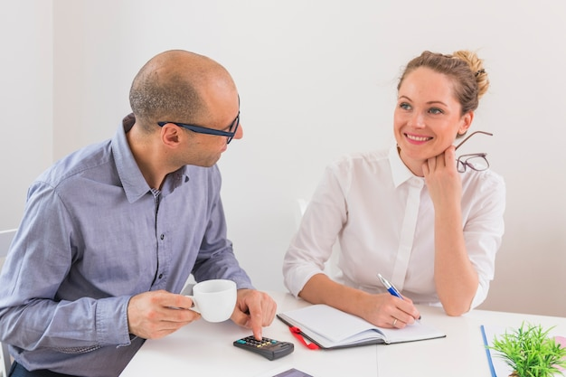 日記とペンで笑顔の実を見ているビジネスマン