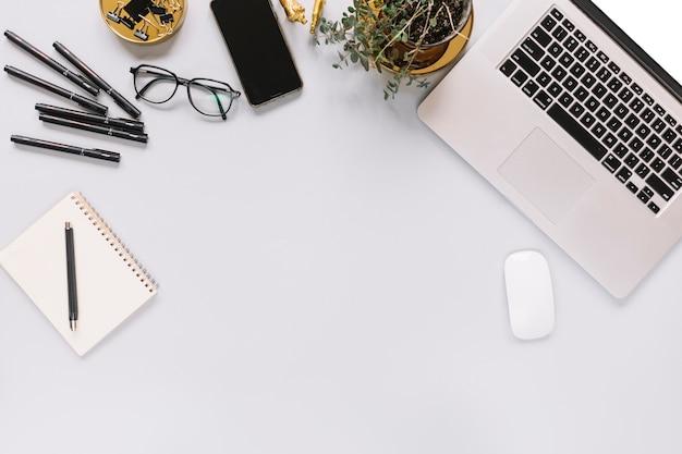 Вид сверху ноутбук и офисные канцелярские принадлежности на белом фоне