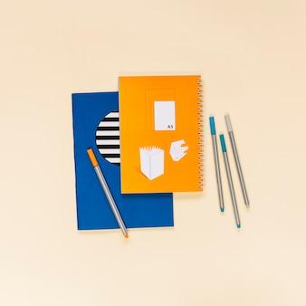 色とりどりのノートの上にカラフルな感じの先端のペンが付いている創造的な