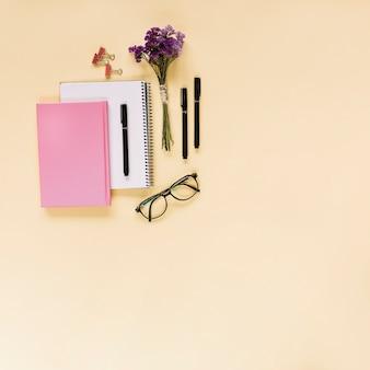 ラベンダーの束;フェルトチップ;ブルドッグ紙クリップ;ベージュの背景に眼鏡とノートブック