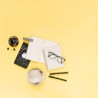 空のノートブック;メガネ、ペン、黄色の背景に空のカップ