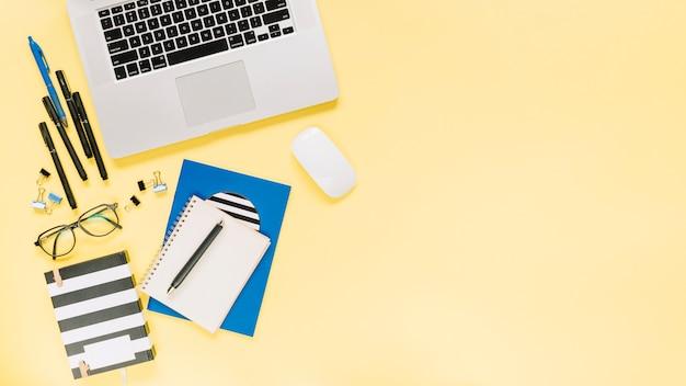 ノートブックとラップトップの文房具の色付きの背景