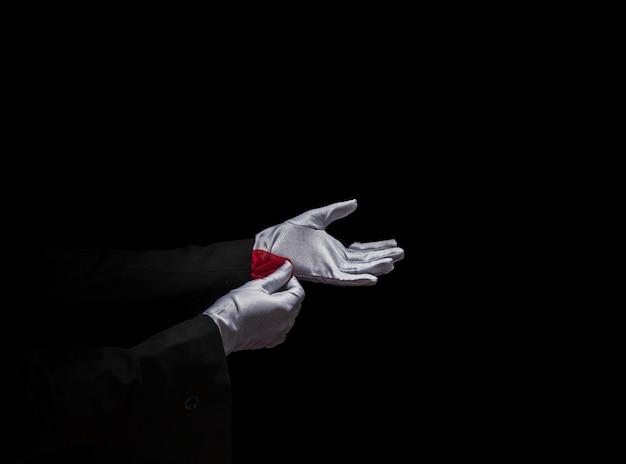 赤いナプキンを袖から黒い背景の上に取り除いている魔術師の手
