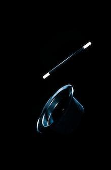 Верхняя черная шляпа и волшебная палочка в воздухе на черном фоне