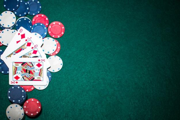 緑の火かき棒の背景の上のカジノの札のロイヤルフラッシュのトランプ