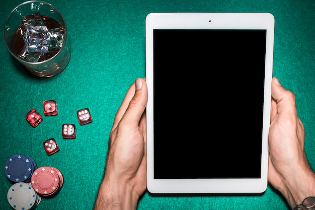 ウィスキー・ガラスのポーカーテーブル上でデジタルタブレットを使用している人間の手