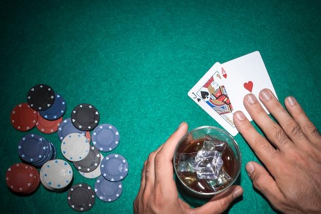 緑のポーカーテーブルにカジノチップを持つジャックとエースカードを見せているポーカープレーヤー