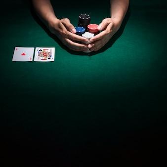カジノのテーブルにポーカーチップのスタックを取る人間の手