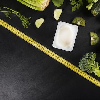 黒の背景にテープや様々な健康な緑の食品を測定する
