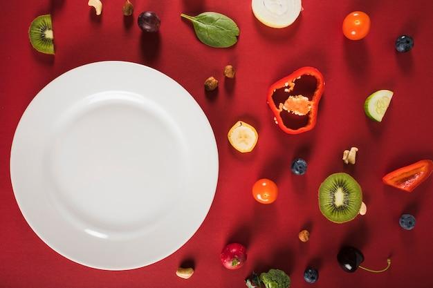 赤い背景にプレートと新鮮な生の食品の高さのビュー