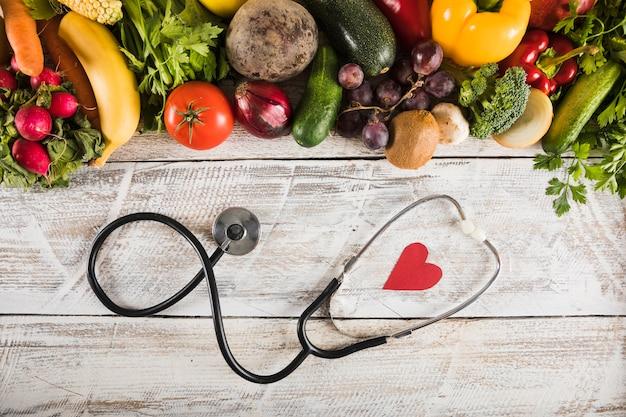 木製の机の上の新鮮な野菜の近くで心臓の形をした聴診器の高められたビュー