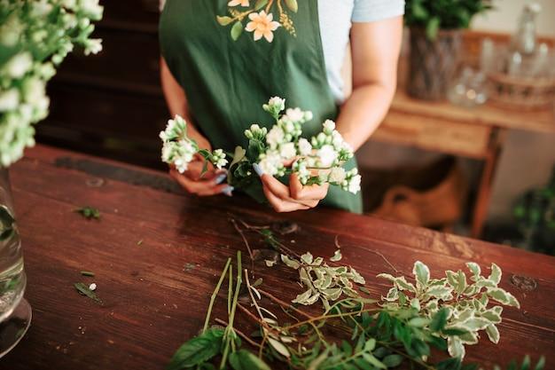 白い花の束を持っている女性の手の中央部のビュー