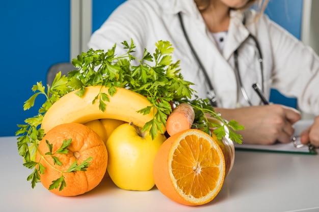 女性の栄養士の前で新鮮なジューシーなフルーツのクローズアップ