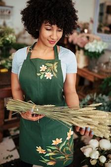 Улыбается молодая женщина, стоя в магазине, держа букет колосок