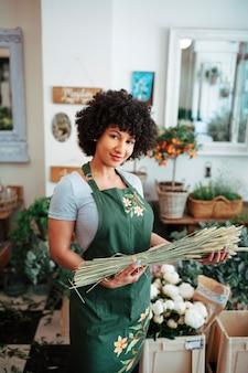 Улыбающийся молодой флорист, держащий колосок в магазине