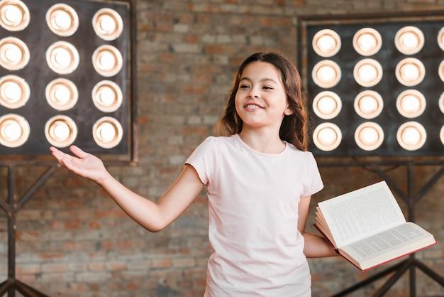 彼女のパフォーマンスを与えるステージライトの前に立っている笑顔の女の子
