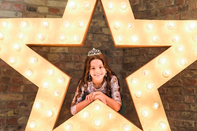 レンガの壁に輝く星に傾いている笑顔の美しい少女
